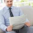 Well dressed young man reading newspaper at home — Stock Photo #39179641