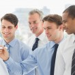 Smiling colleagues watching young businessman write on whiteboar — Stock Photo
