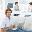 Man using laptop with colleagues at creative office — Stock Photo #39179787