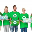 People in recycling symbol t-shirts carrying boxes — Stock Photo #39179799