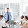 Businessman standing in front of his team at meeting — Stock Photo #39179811