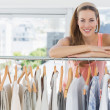 Female fashion designer with rack of clothes in store — Stock Photo #39179845