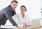 Confident smiling business couple with laptop — Stock Photo