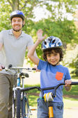 Smiling man with his son riding bicycles — Stock Photo
