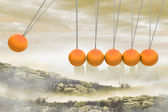 Newtons cradle above city in mountains — Stock Photo