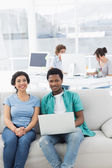 Couple using laptop with colleagues at creative office — Stock Photo