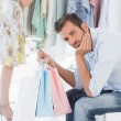 Bored man with shopping bags while woman by clothes rack — Stock Photo #39180033