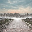 Stony path leading to large city on the horizon — Stock Photo