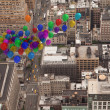 Many colourful balloons above city — Stock Photo #39180265