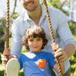 Happy father pushing boy on swing — Stock Photo