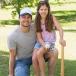 Father and daughter holding baseball bat in park — Stock Photo