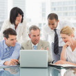 Happy business people gathered around laptop looking at it — Stock Photo #39181019