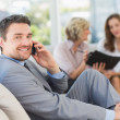 Businessman on call with female colleagues in background — Stock Photo #39181027