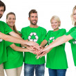 People in recycling symbol t-shirts with hands together — Stock Photo #39181173
