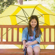 Girl sitting on park bench with an umbrella — Stock Photo #39181365