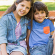 Young boy and girl sitting on park bench — Stock Photo