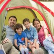 Stock Photo: Couple with kids sitting in the tent at park