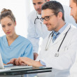 Group of concentrated doctors using laptop — Stock Photo