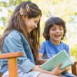 Side view of kids reading book on park bench — Stock Photo