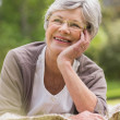 Smiling senior woman lying at park — Stock Photo