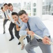 Group of business people pulling rope in office — Stock Photo #39182445