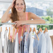 Beautiful female fashion designer with rack of clothes in store — Stock Photo #39182709