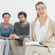 Female financial adviser with young couple in background — Stock Photo