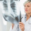 Serious female doctor examining x-ray — Stock Photo
