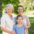 Smiling woman with grandmother and granddaughter at park — Stock Photo