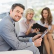 Businessman using digital tablet with colleagues at home — Stock Photo #39183133