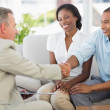 Young couple shaking hands with salesman on the couch — Stock Photo #39183185