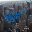 Many colourful balloons above city — Stock Photo