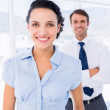 Smiling businesswoman with male colleague in background — Stock Photo