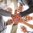 Stock Photo: Cheerful business team looking down at camerwith hands tog