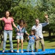 Happy family jumping high on trampoline in park — Stock Photo #39184983