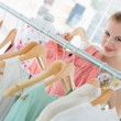 Happy female customer selecting clothes in store — Stock Photo #39185009