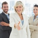 Confident businesswoman offering handshake with team — Stock Photo