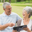 Cheerful senior couple using digital tablet on bench at park — Stock Photo