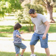 Father and son playing football in the park — Stock Photo