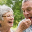 Senior woman feeding strawberry to man — Stock Photo