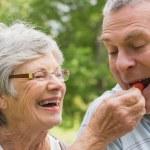 Senior woman feeding strawberry to man — Stock Photo
