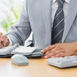 Mid section of a businessman writing in diary — Stock Photo