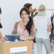 People with clothes donation while using digital tablet — Stock Photo #39185895