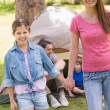 Stock Photo: Mother and daughter with family behind in park