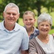 Smiling senior couple and granddaughter at park — Stock Photo