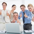 Business colleagues with laptop gesturing thumbs up at desk — Stock Photo