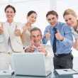 Business colleagues with laptop gesturing thumbs up at desk — Stock Photo #39187219