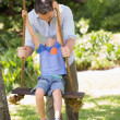 Happy father pushing boy on swing — Stock Photo #39187293