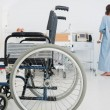 Stock Photo: Doctor helping patient to walk with wheelchair in foreground