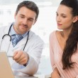 Male doctor showing something on laptop to patient — Stock Photo